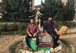 Three students pose on the painted rocks in the garden at Kashkul
