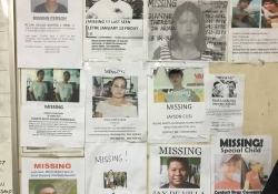 A cropped photo of a bulletin board containing posters of the missing