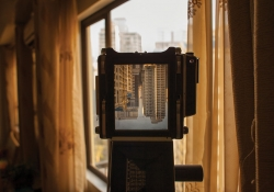 A camera is looking out a window at the city of Manilla. The image of the city is inverted in the camera's viewfinder.