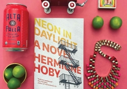 An Instagram style photo of a book surrounded by other objects on a flat pink background