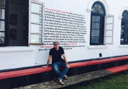 Sergio Chejfec sits in front of an art installation of his writing titled Dissemination of a Novel