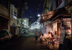 A group of people sit at a table in front of a street vendor in Nagoya, Japan
