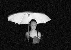 A woman reads a book underneath a lit umbrella