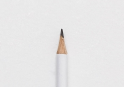 The tip of a white pencil laying on a piece of white paper