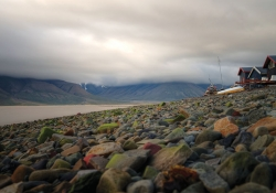 A photo of Svlabard, Noway where a rocky beach in the foregound yields to a bay and foreboding sky in the background
