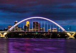 The skyline of Minnepolis seen through an arched bridge suspended over purple water