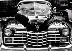 A black and white photograph of an old black Cadillac
