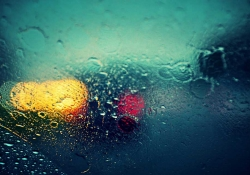 An abstract photograph of a car as seen through a rain streaked window