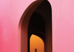 A photograph of a door in a pink wall through which we can see another doorway that opens into an orange room