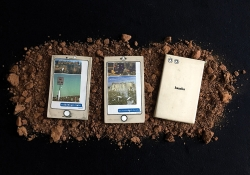 Three disheveled electronic tablets laying on a bed of soil. The third is turned face down