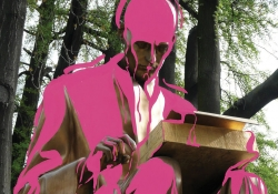 A statue of Indro Montanelli, sitting and reading, with pink digitally added to cover him