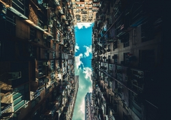 A photo looking upward between two very tall buildings with a blue sky, dotted with clouds, emerging in the thin line between them