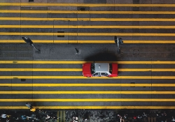 A shot from directly above of a red taxi cab waiting at a street light on a street marked by numerous parallel yellow lines