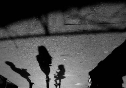 A black and white photograph of human shadows on the pavement