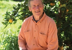 David Holmgren, sitting in the shade of a fruit tree, smiling at the photographer