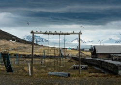 A desolate playground sits in the foreground on dried grass with a glacier in the background