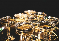 Crystal glasses filled with a gold liquid shot against a dark background