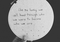 Words needlepointed into cloth on a hoop. The words read I'm so lucky we all lived through who we were to become who we are