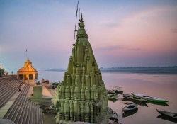 A tall stone temple dominates the shoreline of a wide river, bathed in the colors of sunset