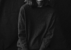 A black and white photo of a woman in a dark sweatshirt and black jean looking at the camera