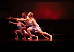 Three dancers lunging to the left, with a dark red background