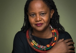 A photograph of Edwidge Danticat, wearing black offset by a colorful scarf, against an olive background