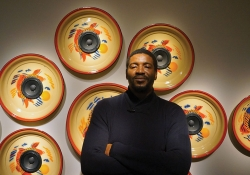 A man stasnds in front of a wall covered in decoratively painted mounted subwoofers