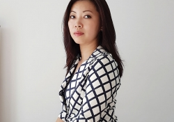 Grace Chia sits against a white background, looking at the camera