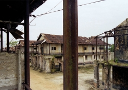 Decrepit buildings stand in an abandoned prison