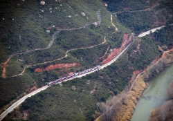A distant shot of a train winding its way through a mountainous countryside