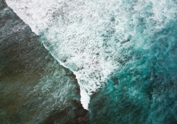 A turbulent wave, capped with foam, from above