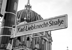 A black and white photograph of a street sign that reads Karl Liebknecht Straße