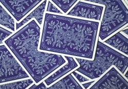 Playing cards with a stylized blue background are scattered on a flat surface