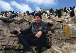 Robin Hemley sits on a outcropping of rock with peguins mingling above him