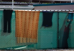 Clothes and other textiles hang on a chain-link fence surrounding tents