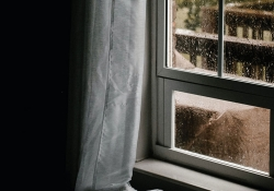 A rain laced window shot from inside a room draped in shade