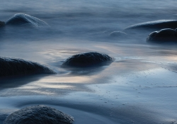A photograph of rocks, mostly submerged in the tide