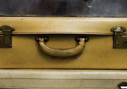 A close up photograph of three aged suitcases stacked flat on one another
