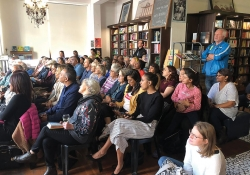 A photograph of an attentive audience, mostly seated in chairs, attending a reading in a bookstore