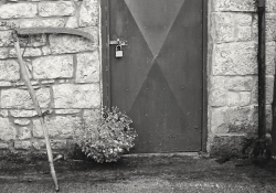 Black and white photograph of a rustic building with a padlock on the door. A scythe leans against the wall just to the left of the door