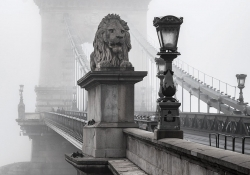 A stone lion adorns the entrance to a bridge that stretches into the background which is swaddled in fog