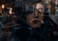 A digitally altered photo of a woman through a window with scenes of the street outside projected on to her face