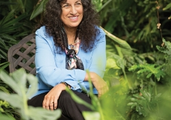 Margarita Engle sits smiling surrounded by plants