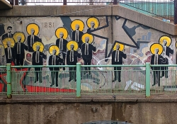 Grafiitti on the side of an off-ramp, dominated by a repeating figure of a man in a suit, sporting a halo like Byzantine iconography