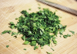 A pile of freshly chopped parsley on a knife-scarred cutting board