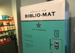 A vending machine. That visible text reads Monkey's Paw Biblio-Mat with the phrase Old & Unusual appearing half-way down the machine