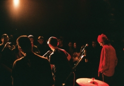 Three musicians stand on a lit stage in a darkened room with the audience standing just inches away