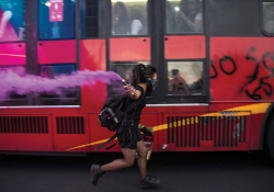 A woman masked in a black bandana runs alongside a bus covered with graffiti carrying a purple flare