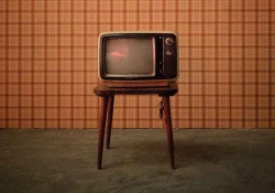 A photograph of an old tube style television on a wooden stand in front of a old-fashioned brown plaid wallpaper