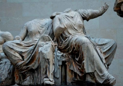 A photograph of a statue of two figures, seated in draped clothing, but headless, and worn down by time and the elements.